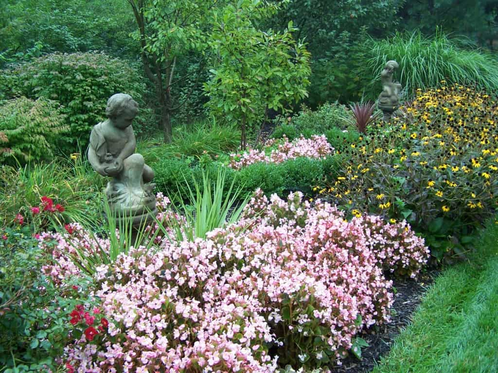 Massing plants around garden statuary is romantic/artistic