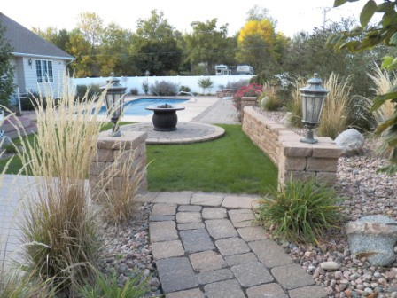 Poolside plantings, patio, and fire pit separate this landscape into several rooms.